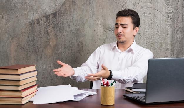 Niezadowolony pracownik wskazujący na kartki i siedzący przy biurku. wysokiej jakości zdjęcie