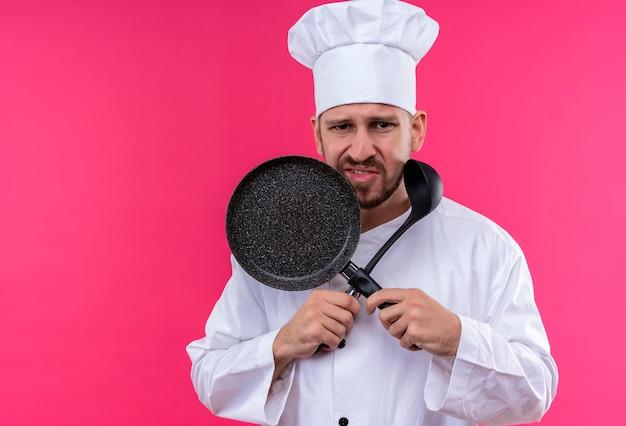 Niezadowolony profesjonalny kucharz mężczyzna w białym mundurze i kapeluszu kucharza, trzymając chochlę do zupy i patelnię stojącą na różowym tle