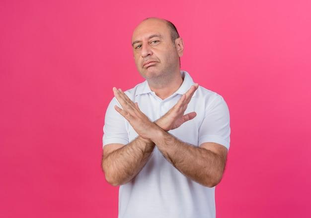 Niezadowolony przypadkowy dojrzały biznesmen trzymając ręce skrzyżowane, nie robiąc żadnego gestu na różowym tle z miejsca na kopię