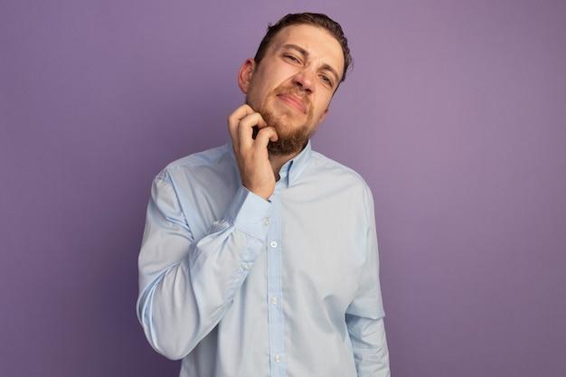 Niezadowolony przystojny blondyn drapie brodę na białym tle na fioletowej ścianie
