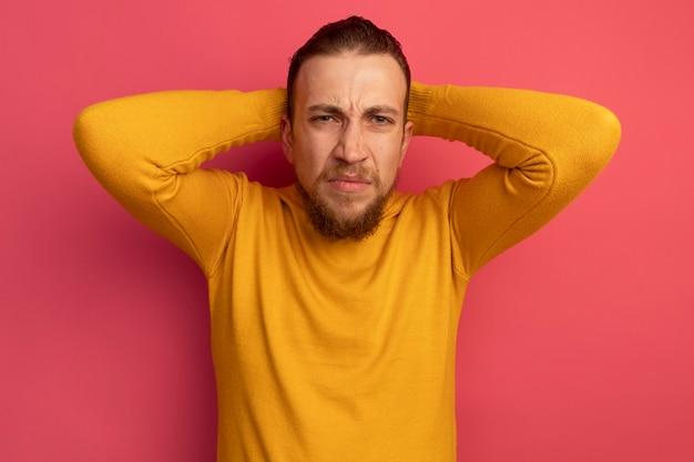 Niezadowolony przystojny blondyn kładzie ręce na głowie z tyłu na białym tle na różowej ścianie