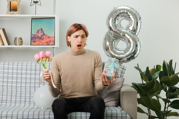 Niezadowolony przystojny facet w szczęśliwy dzień kobiet trzymający kwiaty z obecnym siedzącym na kanapie w salonie