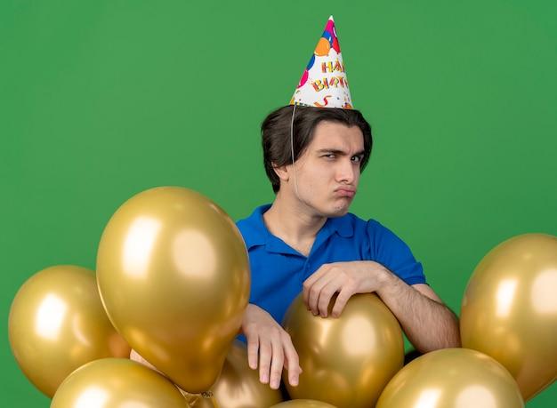 Niezadowolony przystojny kaukaski mężczyzna w czapce urodzinowej stoi z balonami z helem, patrząc na kamerę