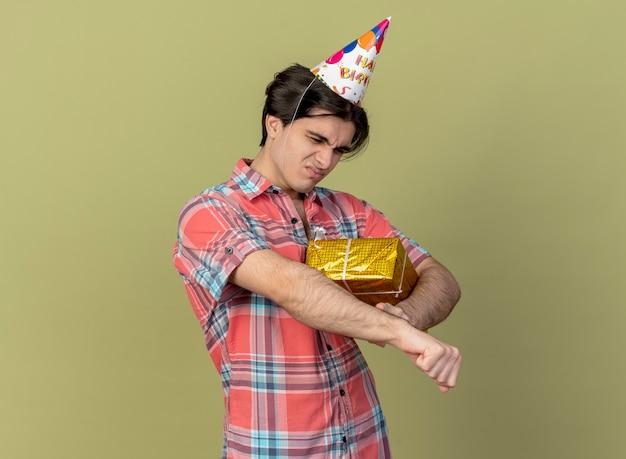 Niezadowolony przystojny kaukaski mężczyzna w czapce urodzinowej trzyma pudełko na prezent