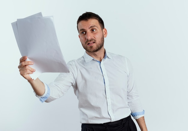 Niezadowolony przystojny mężczyzna trzyma i patrzy na arkusze papieru na białej ścianie