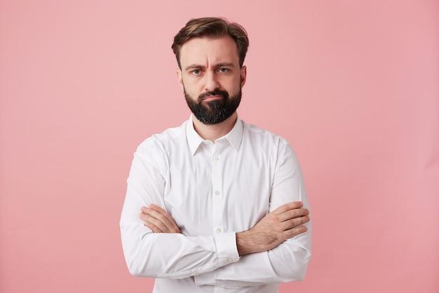 Niezadowolony, przystojny młody brunetka mężczyzna z brodą, trzymając ręce złożone, stojąc przy różowej ścianie, marszcząc brwi i wykręcając usta, ubrany w formalne ubrania