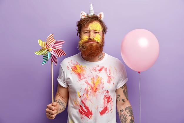 Niezadowolony rudy mężczyzna trzyma wiatrak-zabawkę i balon z helem, ma twarz zabrudzoną żółtymi akwarelami, rudymi włosami i brodą, odizolowaną na fioletowej ścianie. przygotowanie przyjęcia
