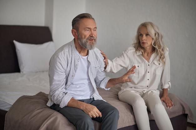 Niezadowolony siwy mężczyzna rasy kaukaskiej siedzący na łóżku odpychający żonę po kłótni