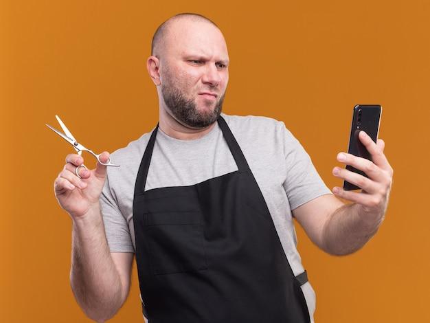Niezadowolony słowiański fryzjer w średnim wieku w mundurze trzymający nożyczki i patrząc na telefon w dłoni odizolowany na pomarańczowej ścianie
