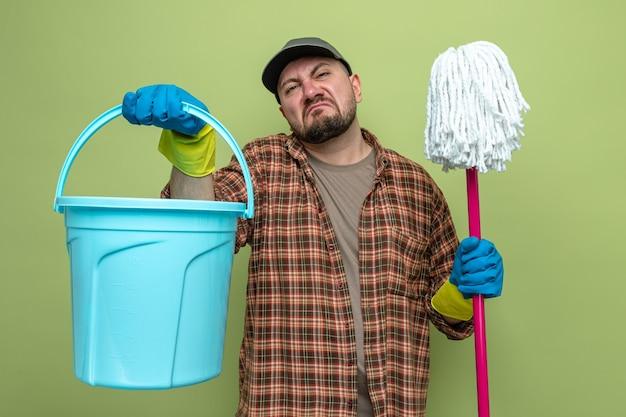 Niezadowolony słowiański sprzątacz w gumowych rękawiczkach trzymający wiadro i mop