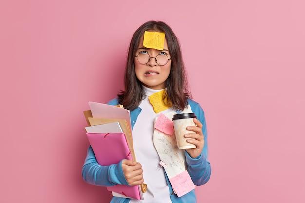 Niezadowolony student gryzie usta i patrzy w górę z niezadowolonym zmęczonym wyrazem twarzy napoje kawa na wynos praca z papierami nosi okrągłe okulary.