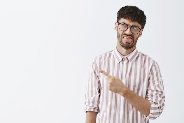 Niezadowolony stylowy brodaty facet w okularach pozujący przy białej ścianie