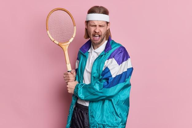 Niezadowolony tenisista trzyma rakietę zdenerwowany, aby przegrać rywalizację, robi niezadowolony grymas ubrany w sportowy strój.
