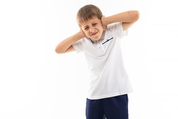 Niezadowolony uczeń nie chce nic słyszeć, kapryśnie zakrywa uszy rękami