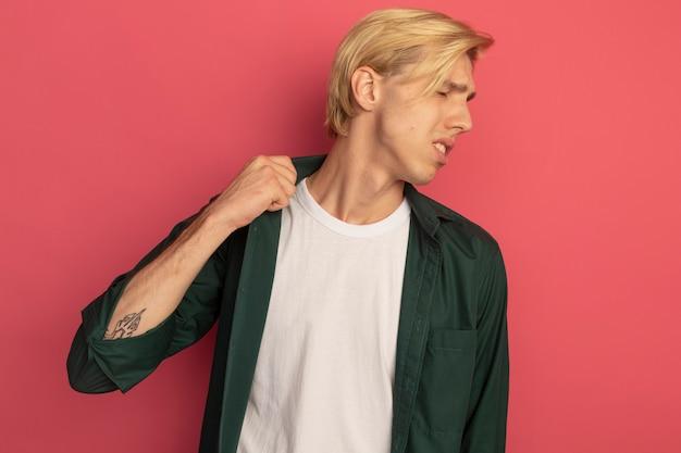 Niezadowolony z zamkniętymi oczami młody blondyn ubrany w zieloną koszulkę z kołnierzykiem na różowym tle