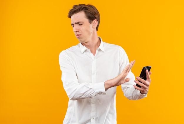 Niezadowolony z zamkniętymi oczami młody przystojny facet w białej koszuli trzymający telefon odizolowany na pomarańczowej ścianie