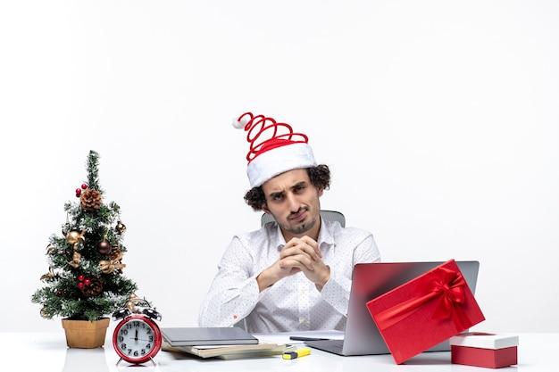Niezadowolony zajęty dumny młody biznesmen z zabawnym czapką świętego mikołaja świętuje boże narodzenie w biurze na białym tle
