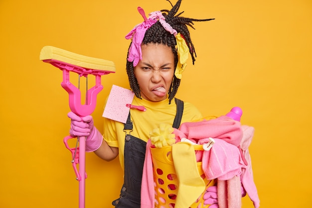 Niezadowolony, zajęty sprzątacz domu uśmiecha się z niechęcią, trzyma mopa do mycia podłogi, zbiera brudne pranie w koszu izolowanym nad żółtą ścianą