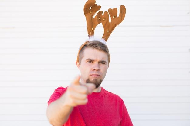 Niezadowolony zły człowiek w rogach jelenia bożego narodzenia, wskazując na widza