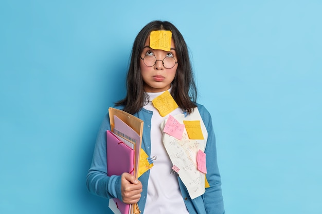 Niezadowolony, zmęczony student z azji, skoncentrowany powyżej, ma smutny wyraz twarzy, nosi okulary korekcyjne, trzyma teczki z kartkami przypięte spinaczami do papieru.