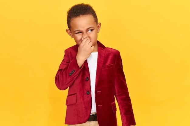 Niezadowolony zniesmaczony chłopak zwymiotuje z powodu nieprzyjemnego zapachu