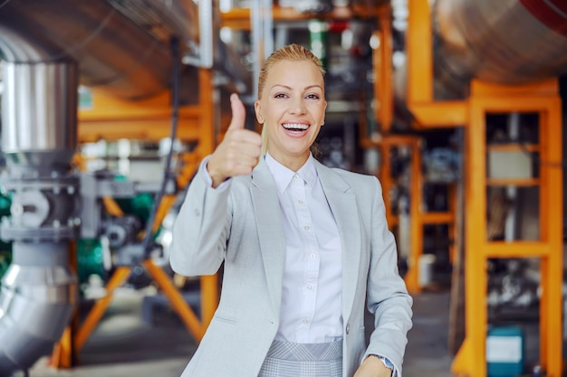 Niezależna dyrektorka generalna w średnim wieku, odnosząca sukcesy, ubrana w garnitur, stojąca w ciepłowni i pokazująca kciuki do góry