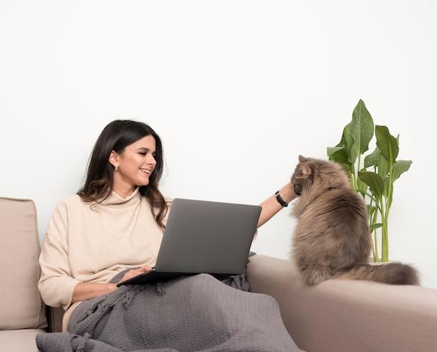 Niezależna kobieta bawić się z kotem podczas gdy pracujący