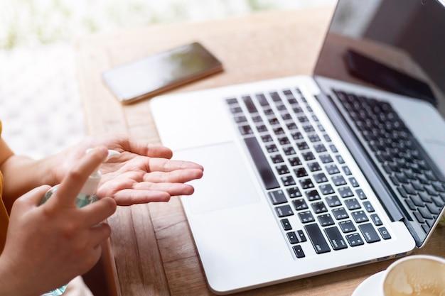 Niezależna kobieta biznesu, używając ręcznie środka dezynfekującego do czyszczenia dłoni, aby zapobiec wirusowi i pracy z laptopem
