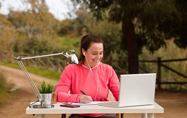 Niezależna kobieta pracuje na swoim komputerze na zewnątrz, w przyrodzie
