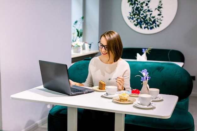Niezależna kobieta pracuje z laptopem w kawiarni. młoda piękna poważna kobieta z krótkim ciemnym włosy w szkłach pracuje na laptopie w kawiarni. ufna młoda kobieta w mądrze przypadkowej odzieży pracuje na laptopie