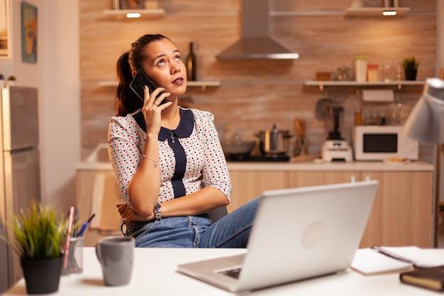 Niezależna kobieta rozmawia przez telefon z klientem późno w nocy z domowej kuchni. pracownik korzystający z nowoczesnych technologii o północy wykonujący nadgodziny w pracy, biznesie, karierze, sieci, stylu życia.