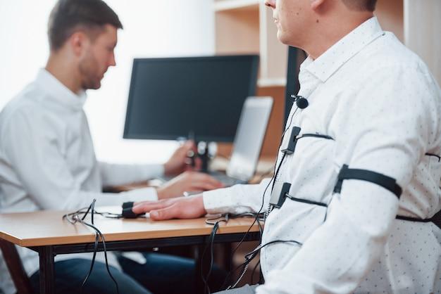 Niezależne badanie wariografem. podejrzany mężczyzna mija w biurze wykrywacz kłamstw. zadawać pytania