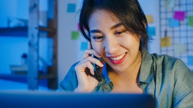 Niezależne kobiety z azji za pomocą laptopa rozmawiają przez telefon zajęty przedsiębiorca pracujący na odległość w salonie.
