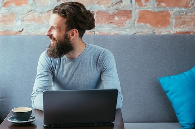 Niezależny autor treści pracujący w kawiarni przy użyciu laptopa.