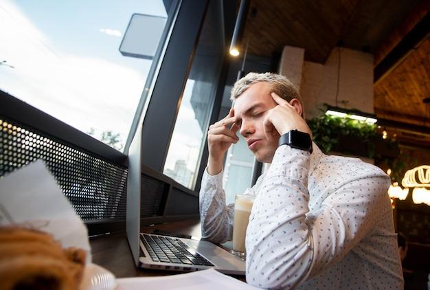 Niezależny człowiek o migrenie w kawiarni. mężczyzna pracujący w kawiarni przed laptopem, cierpiący na przewlekłe codzienne bóle głowy. młody mężczyzna trzyma bolesną głowę i źle się czuje. niewyraźne pyszne jedzenie z przodu.