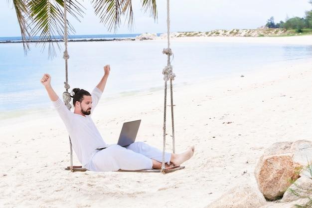 Niezależny mężczyzna ubrany na biało siedzi na plaży huśtawka z laptopem