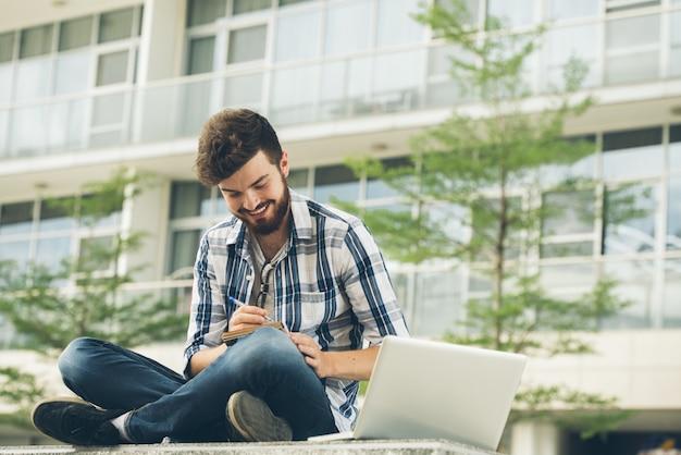 Niezależny pracownik pełen kreatywnych pomysłów, siedzący w lotosie, robi notatki na zewnątrz