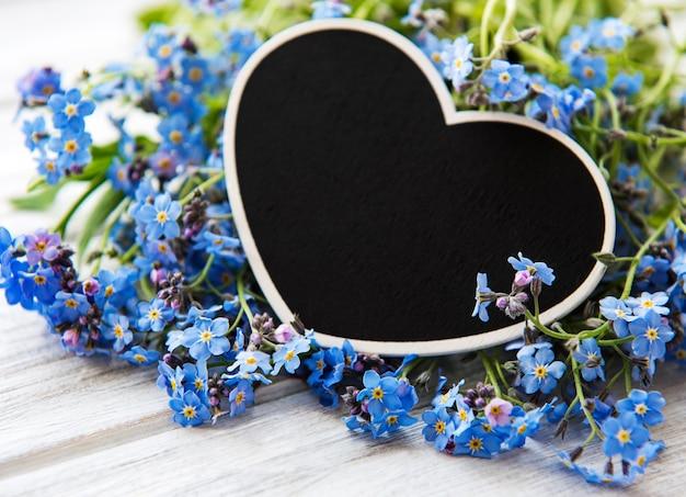 Niezapominajka kwiaty i czarna deska w kształcie serca na białym drewnianym tle