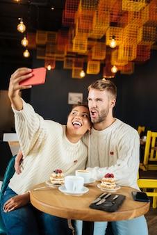 Niezapomniane zdjęcie. zabawna śliczna para ubrana w te same swetry z dzianiny robiąca niezapomniane zdjęcie siedząc w kawiarni