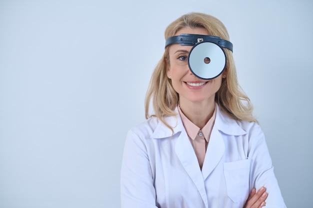 Niezawodność. uśmiechnięta dość pewna siebie kobieta otolaryngolog o długich blond włosach z lusterkiem do badania stojącym z rękami skrzyżowanymi na białym tle