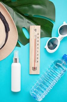 Niezbędne akcesoria na letnie upały: okulary przeciwsłoneczne, czapka, krem do opalania i butelka wody.