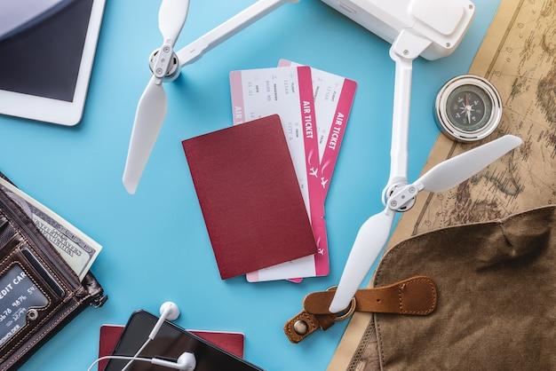 Niezbędne rzeczy do lotu na wakacjach. bilety lotnicze, paszport, karta kołyski, telefon, dron quadcopter, aparat, mapa świata na niebieskim tle