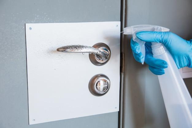 Niezbędne towary podczas epidemii - zapobieganie i ochrona rozprzestrzeniania się koronawirusa covid-19. ręcznie w rękawiczkach dezynfekujących powierzchnie środkiem dezynfekującym w domu. czyszczenie przeciwko wirusowi zapalenia płuc.