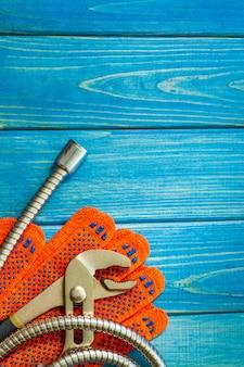 Niezbędny zestaw narzędzi dla hydraulików na niebieskiej drewnianej ścianie