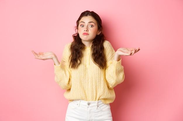 Niezdecydowana dziewczyna wzrusza ramionami i nieświadomie patrzy w kamerę, stojąc nieświadomie na różowej ścianie. skopiuj miejsce