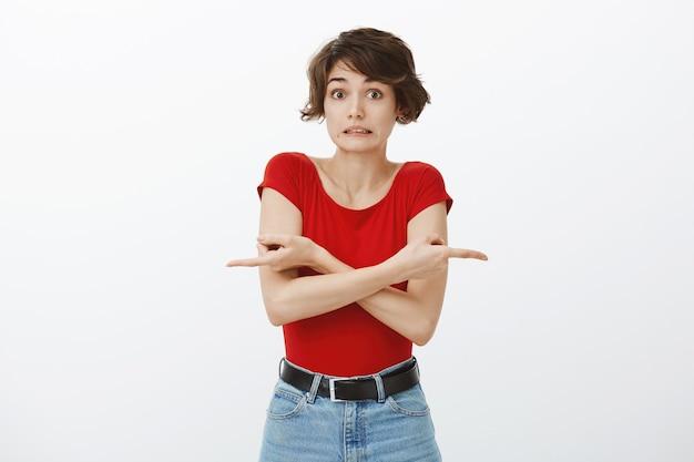 Niezdecydowana, głupia młoda kobieta wskazująca palcami w bok, wyglądająca na nieświadomą, potrzebuje pomocy przy wyborze