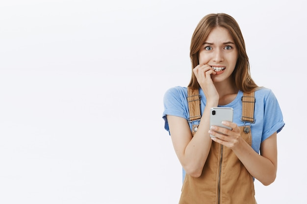 Niezdecydowana ładna nowoczesna dziewczyna gryzie palec niepewnie podczas wysyłania wiadomości sms na smartfona