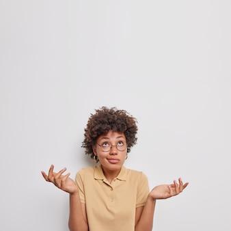Niezdecydowana, niezdecydowana, kręcona młoda afroamerykanka rozkłada dłonie, czuje wątpliwości, skupiona na górze, czuje niepewność podczas podejmowania decyzji, nosi swobodną beżową koszulkę na białym tle na białym tle