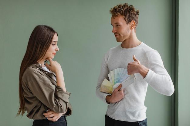 Niezdecydowana para rozmawia o remoncie domu przy użyciu palety farb