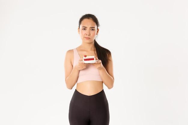 Niezdecydowana śliczna azjatycka sportsmenka z zaniepokojonym ciastem, chce jeść słodycze, myśli o kaloriach i masie ciała po treningu, białe tło.